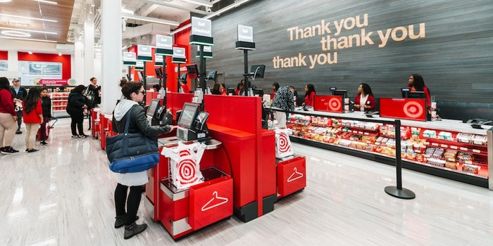 The interior of a Target store where customers are standing at self-checkout kiosks.