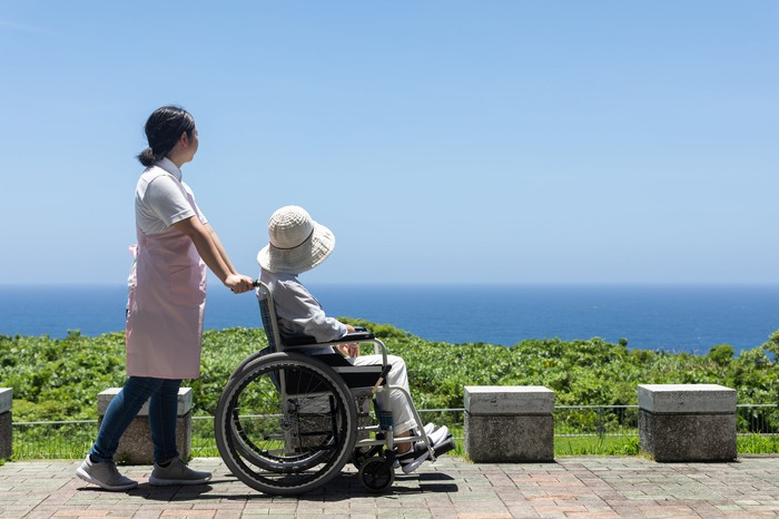 A caregiver pushes an elderly woman in a wheelchair.