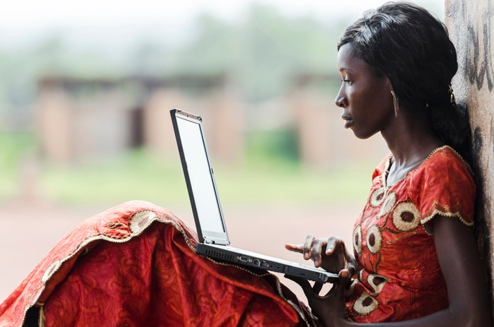 A young African woman uses a laptop outside.