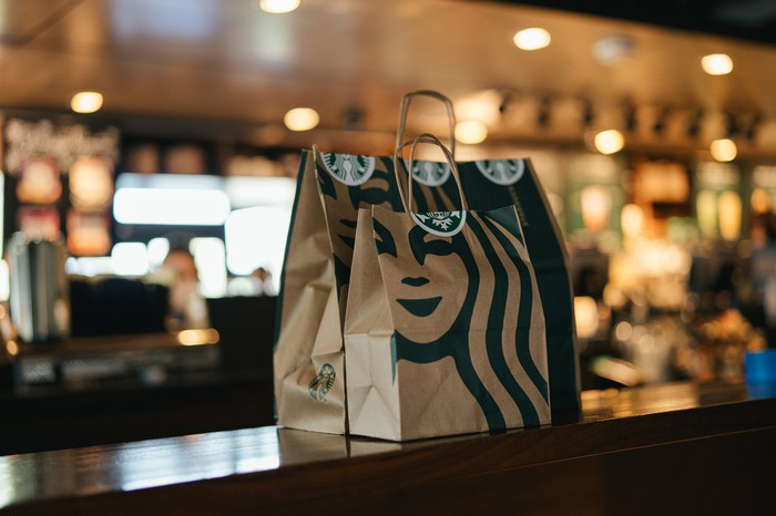 Two Starbucks bags wait on the store counter for pickup.