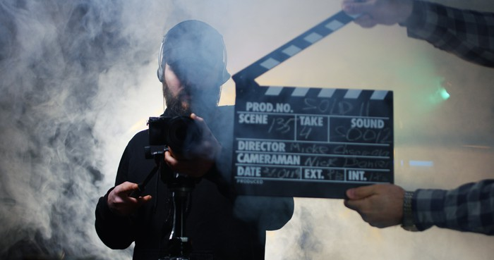 Photo of a cameraman and a film set clapboard in heavy fog.