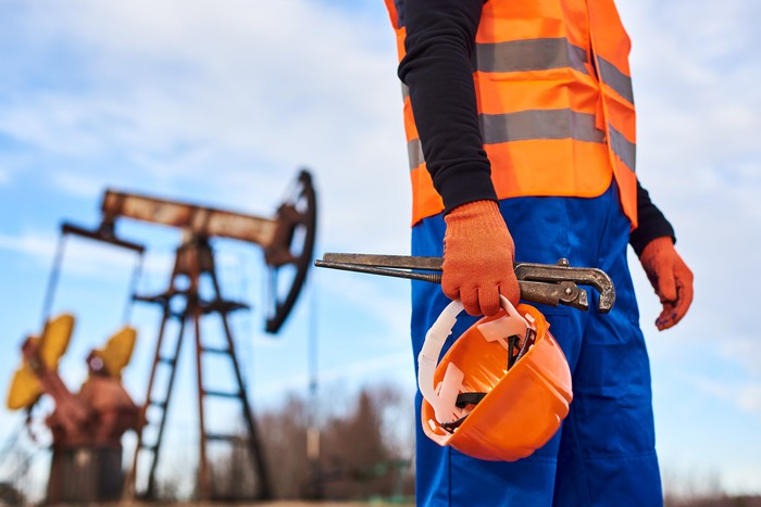 oil field service worker in front of rig