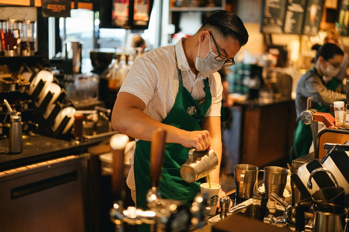 A Starbucks barista wears a mask and pours a coffee beverage.