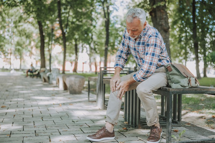 A senior man rubs his knee while sitting on a park bench.