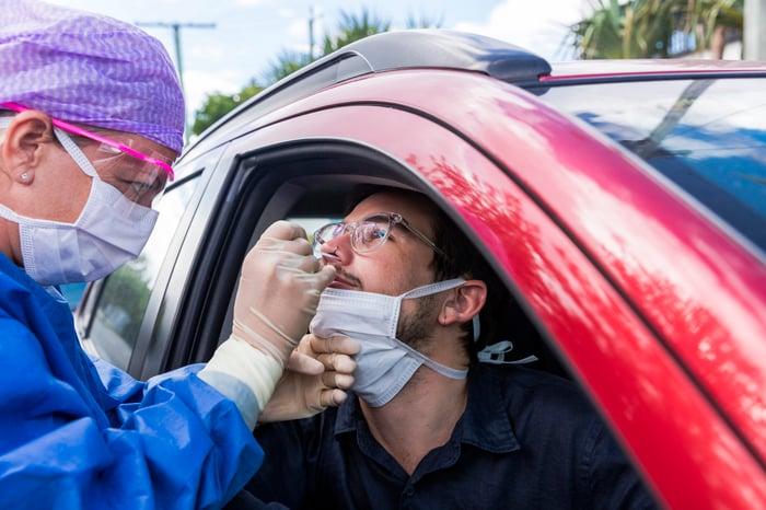 Man in a car getting a nasal swab test