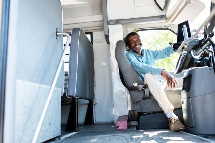 Smiling older male bus driver