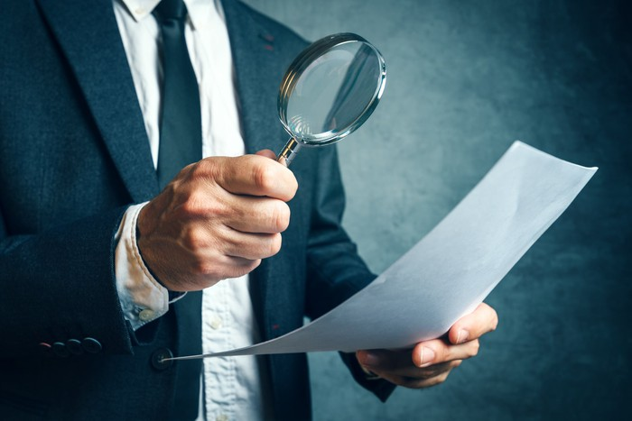 A person in a business suit is inspecting a piece of paper with a magnifying glass.