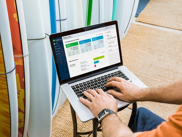 A small business owner using QuickBooks Online on a laptop