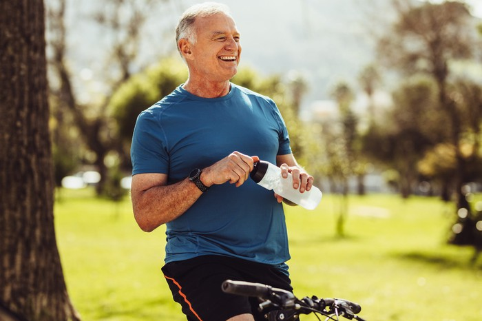 Smiling older man outdoors holding water bottle