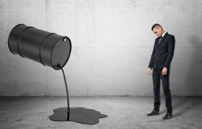 A frowning man stands next to an oil drum spilling oil on the ground.