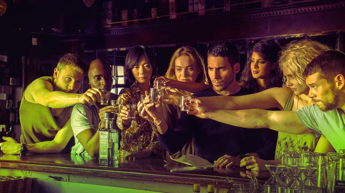 The cast of Sense8 raising glasses to make a toast at a bar counter.