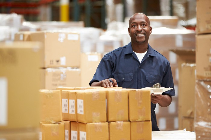 Man smiling while standing beside parcels in a warehouse