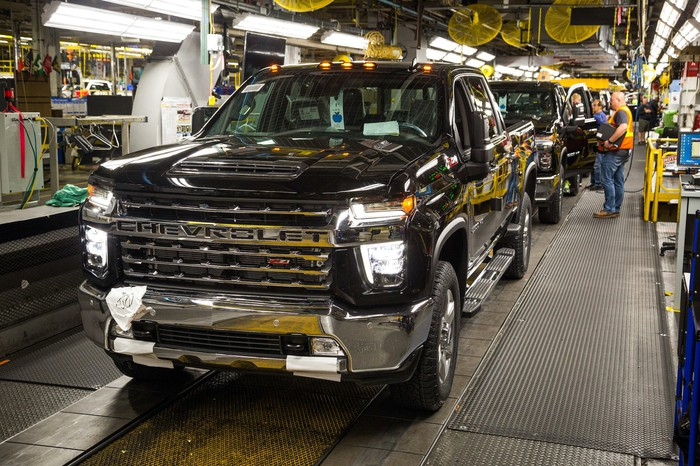 Pickup trucks on a factory assembly line.