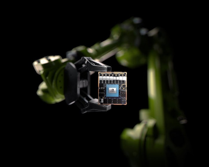 A robotic arm holding an NVIDIA chip.