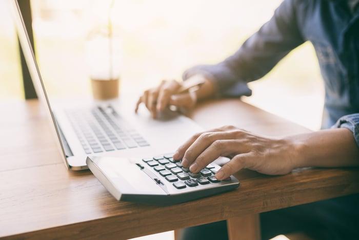 Man at laptop typing on calculator