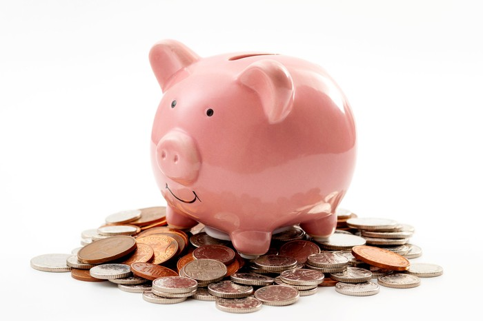 A piggy bank stands on a pile of small change.