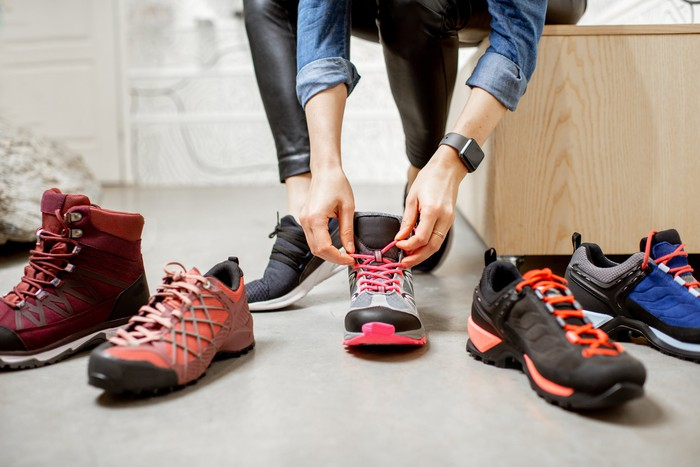 A person holds the laces of a shoe that sits between several other athletic shoes.