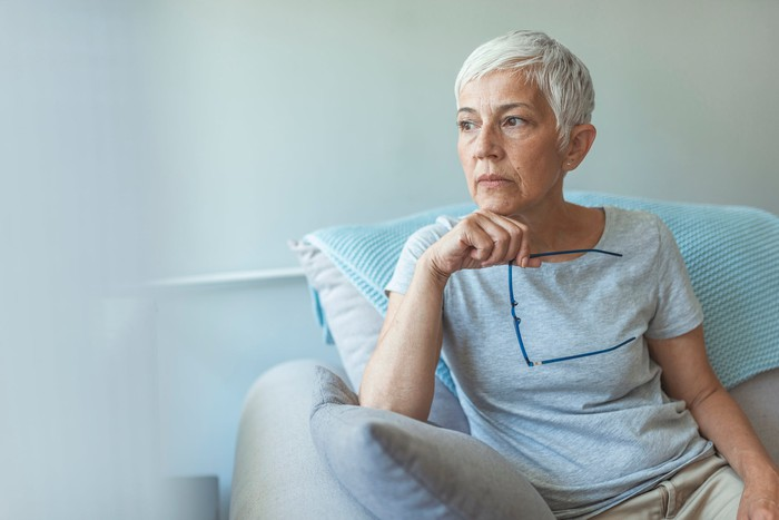 Older woman with serious expression sitting in chair holding eyeglasses
