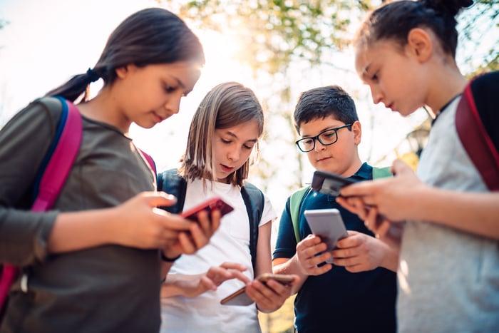 Enfants jouant à des jeux vidéo sur smartphones