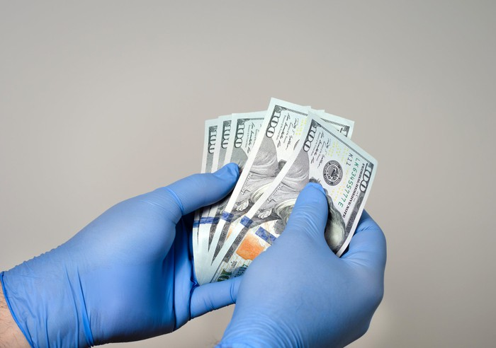 Gloved hands holding five $100 bills