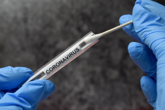 Gloved hands holding cotton swab and vial with coronavirus printed on the label