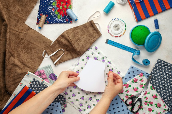 A craft table viewed from above as someone makes face masks out of various fabrics
