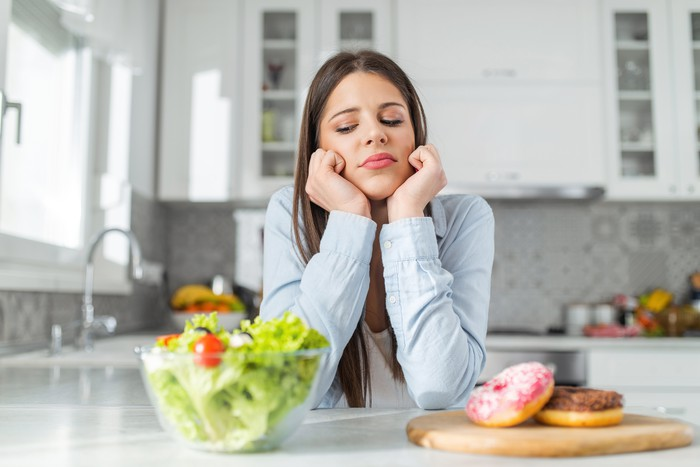 Woman trying to decide between salad and donut.