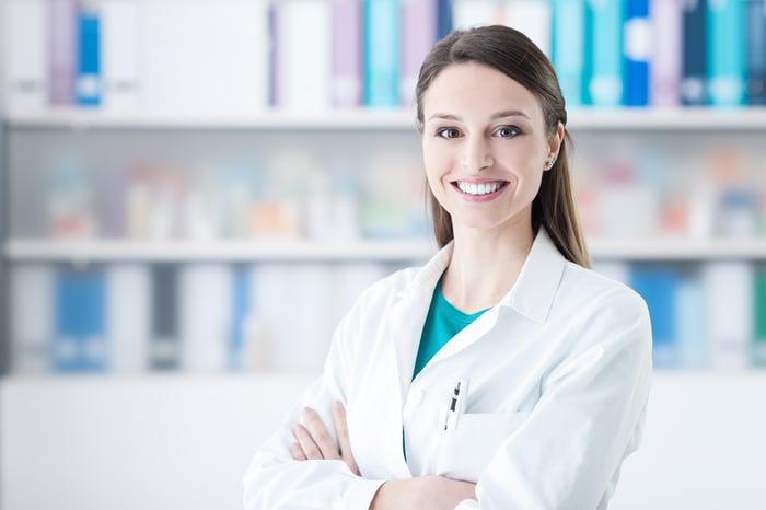 Doctor standing by pharma shelf.