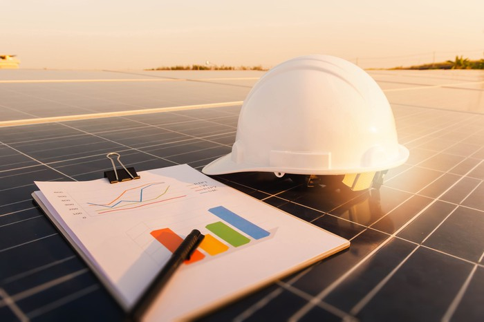 An engineer's hard hat and clipboard rest on solar panels.