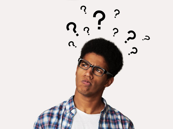 Confused man with question marks above his head.