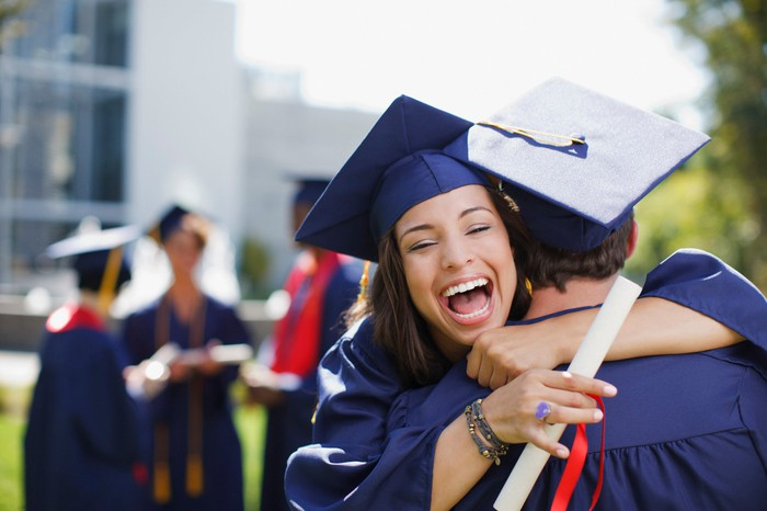 People in graduation caps and gowns hugging each other