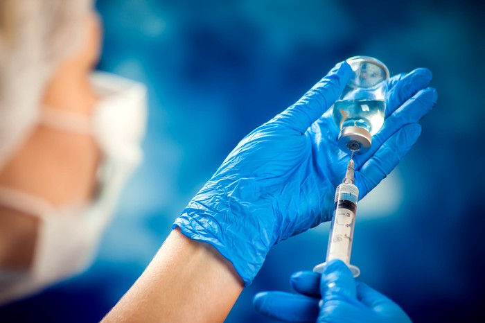 Healthcare professional holding syringe and vaccine bottle