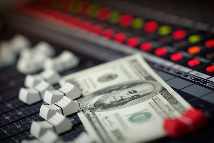 A hundred dollar bill sitting on a mixing board.