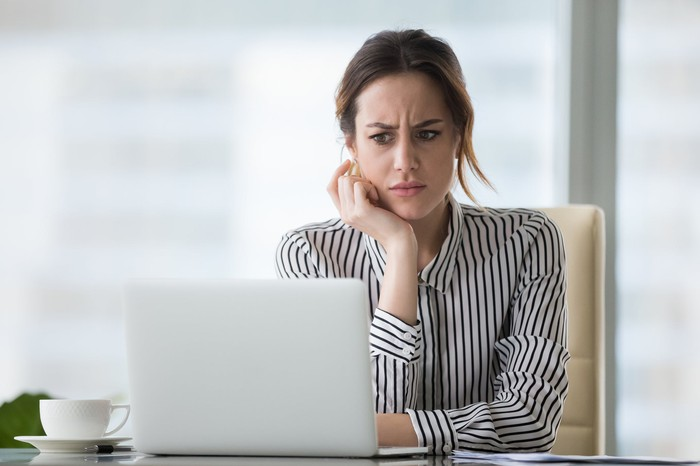 A woman looking at her laptop, perplexed