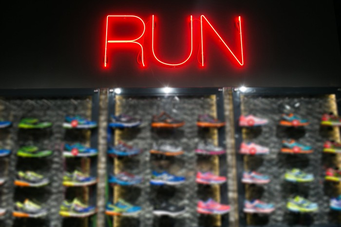 A wall of running shoes in a retail store, under the word Run in neon lighting