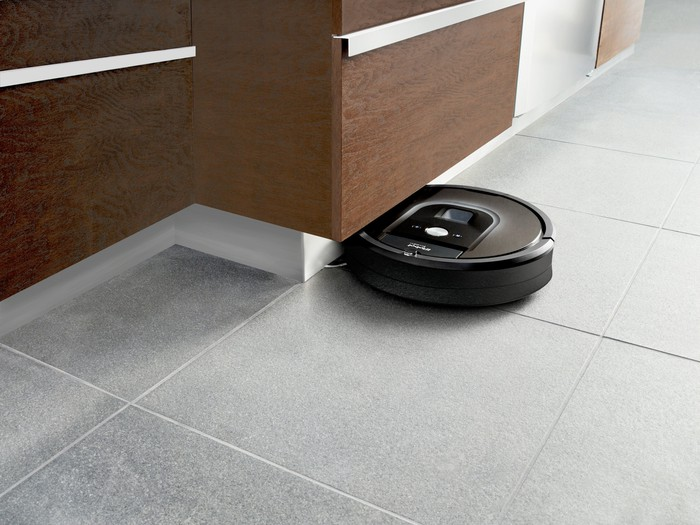 A iRobot Roomba vacuum cleans under a cabinet toe-kick.