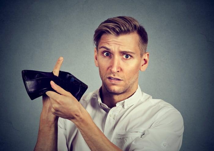 A man sticks his finger through an empty wallet.