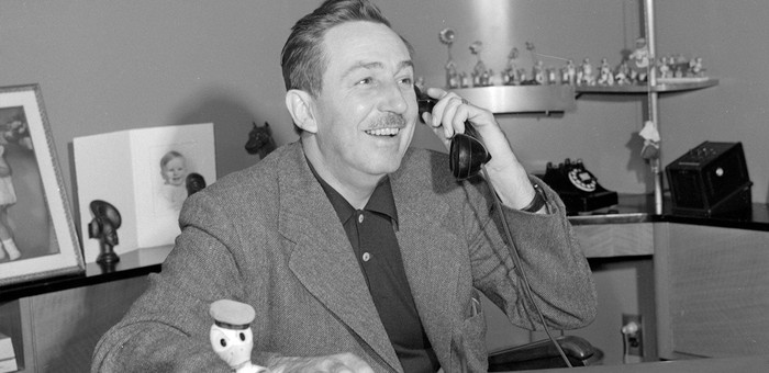 Black and white photo of Walt Disney talking on the phone.