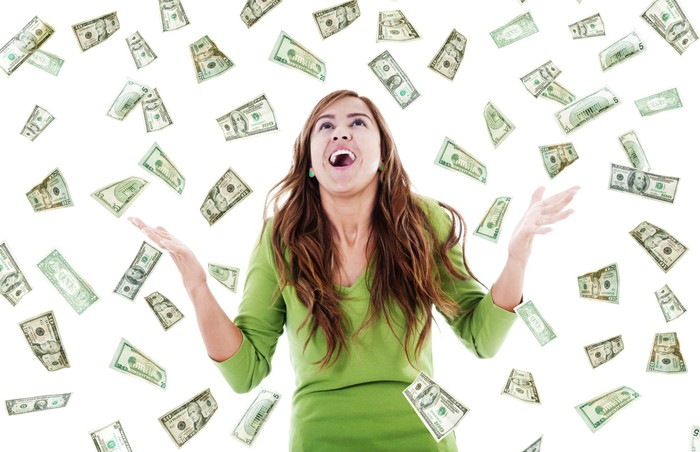 Woman with her hands up as money falls out of the sky around her.