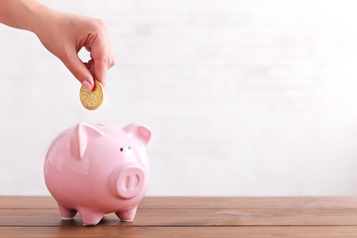 Hand dropping a coin into a pink piggy bank.