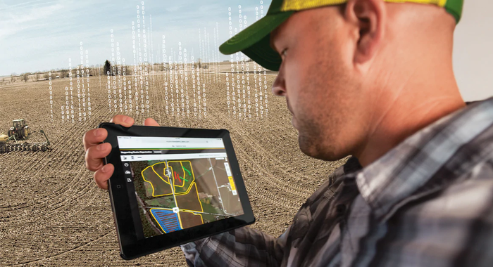 A farmer using Deere's telematics to remotely guide equipment.