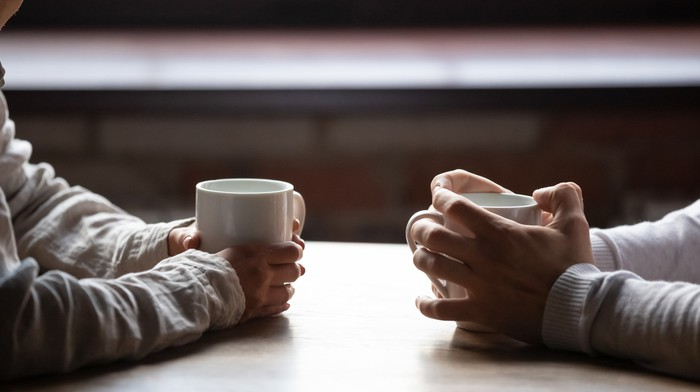 closeup on two pairs of  hands holding white cofee  mugs on a coffeeshop table.
