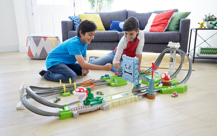 Two young boys playing with a Hot Wheels racing track.