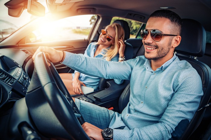 Two smiling people in a car.