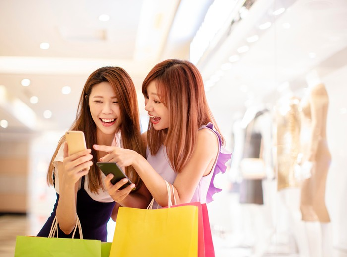 Two young women check a smartphone app while shopping.