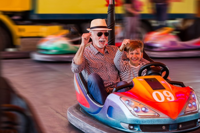 child and grandparent riding bumper cars