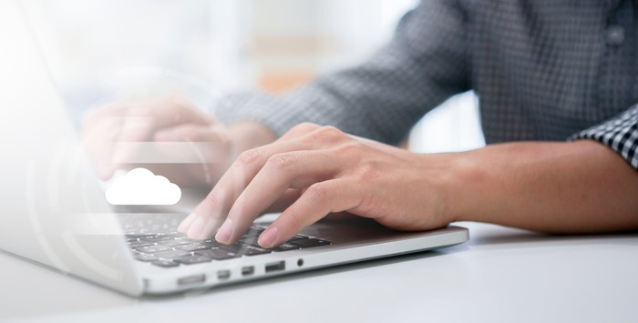 A person's hands are shown on a laptop with a cloud image above them.