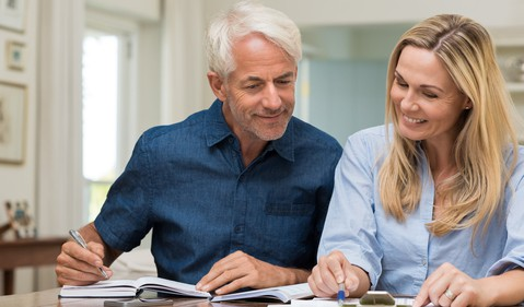 mature couple discussing finances with pens and paper