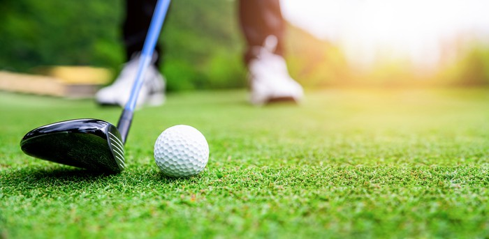 A close-up of a golf club about to hit a golf ball.