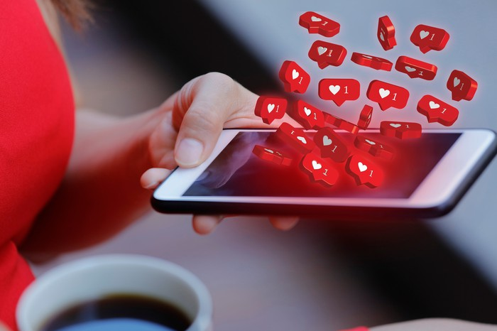 A woman on social media on her phone with hearts representing likes.